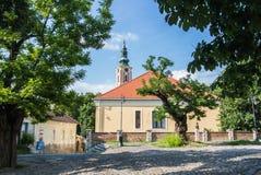 SZENTENDRE, UNGARN - 26. JULI 2016: Altes Haus mit Ziegeldach und eine Kirche in der Mitte von Szentendre Stockbilder