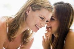 szepczą uśmiechać dwie kobiety Zdjęcia Royalty Free