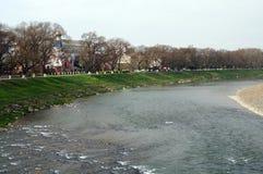 Szeroka rzeka która płynie między piaskowatą plażą Zdjęcie Stock