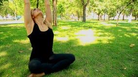 Szeroka strzał młoda kobieta robi joga w parku zbiory