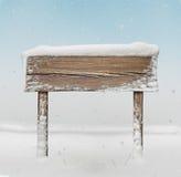 Szeroki drewniany kierunkowskaz z śniegiem na nim i opadzie śniegu Fotografia Royalty Free