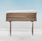 Szeroki drewniany kierunkowskaz z mniej śniegu na nim i opadzie śniegu Obraz Stock