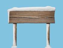 Szeroki drewniany kierunkowskaz z mniej śniegu odizolowywającego na błękicie Zdjęcie Royalty Free