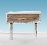 Szeroki drewniany kierunkowskaz z śniegiem i niebieskim niebem Obrazy Royalty Free