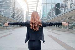 Szeroki kąta strzał tylnego widoku bizneswomanu atrakcyjna młoda Azjatycka pozycja i rozciąganie ręki przy miastowym budynku społ Obrazy Stock