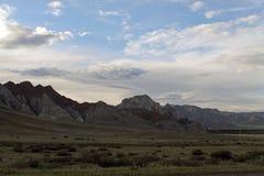 Szeroki step z żółtą trawą pod niebieskim niebem z bielem chmurnieje Sayan góry Syberia Rosja Fotografia Royalty Free