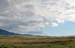 Szeroki step z żółtą trawą pod niebieskim niebem z bielem chmurnieje Sayan góry Syberia Rosja Obrazy Royalty Free
