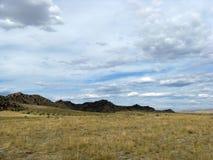 Szeroki step z żółtą trawą pod niebieskim niebem z bielem chmurnieje Sayan góry Syberia Rosja Zdjęcia Stock
