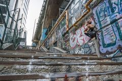 Szeroki strzał Uliczna punkowa dziewczyna w Miastowym Dziewczyny obsiadanie na schodkach malował z graffiti pod mostem zdjęcie stock