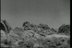 Szeroki strzału kowboj na horseback cwałowaniu przez pasma górskiego zbiory