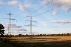 Szeroki widok na elektryczność pilonach pod bielem i niebieskim niebem chmurnieje na skoszonym polu w geeste emsland Germany zdjęcia royalty free