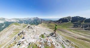 Szerokiego kąta panoramy A mężczyzna powietrzni stojaki na wierzchołku w górach Fotografia Royalty Free