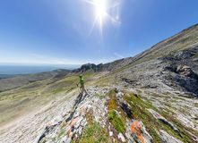 Szerokiego kąta panoramy A mężczyzna powietrzni stojaki na wierzchołku w górach Zdjęcia Royalty Free