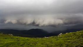 Szerokiego lata halna panorama przed burzą Ciemna podeszczowych chmur niska nadmierna zielona trawiasta skalista dolina i odległy Zdjęcie Stock