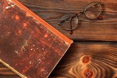 Szkła i książka na drewnianym tle zdjęcia stock