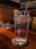 Szkło lodowa woda z cytryną na drewnianym stole w restauracyjnym położeniu Żadny ludzie fotografia royalty free