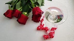 Szkło zawijający z czerwonymi sercami tasiemkowymi z wermutem stading fotografia stock