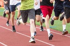 Szkół średnich chłopiec biega w grupie na czerwieni tropią obraz stock