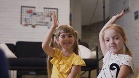 Szkół podstawowych dziewczyny podnoszą ich ręki odpowiadać pytanie który pytał ich nauczyciela Dwa szkolnego dziewczyny zabawy dź zbiory