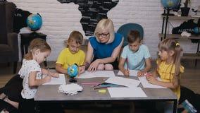 Szkół podstawowych piękni dzieci rysuje w sala lekcyjnej z nauczyciela pomagać Dziecko remisu rysunek z nauczycielem przy zbiory wideo