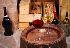 Szkła i butelki wino na starej baryłce w wino lochu czerwony i biały Obraz Royalty Free