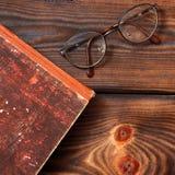 Szkła i książka na drewnianym tle zdjęcia royalty free