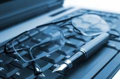 Szkła i pióro na laptopie obraz stock