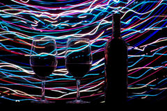Szkła i wino butelka na czarnych śladach i tle Zdjęcia Stock