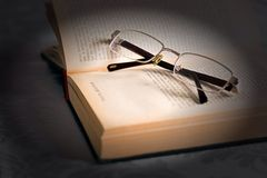 Szkła na starej rozpieczętowanej książce Obrazy Royalty Free
