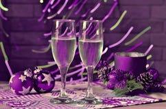 Szkła szampańskie i Bożenarodzeniowe dekoracje purpury obrazy royalty free