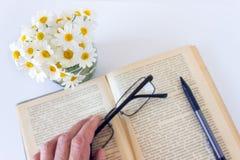 Szkła w ręce na starej książce otwierają na bielu stołu tle obraz stock