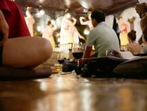 Szkła wino na siedzącej podłoga w w połowie turyści przychodzi cieszyć się tradycyjnego Północnego Tajlandzkiego występ i łomotać obraz stock