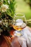 Szkła wypełniali z brandy, jeden szkło na stole obok kwiatu przygotowania zdjęcie stock