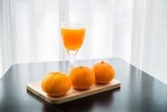 Szkło świeżo naciskający sok pomarańczowy z trzy pomarańcze Fotografia Stock