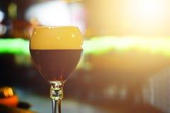 Szkło świeży ciemny piwo na nieociosanym karczemnym tle Fotografia Royalty Free