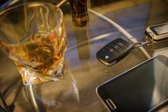 Szkło alkoholicznego napoju i samochodu klucz na stole, lekki tło obrazy stock