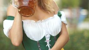 Szkło Bawarski piwo w rękach młoda kelnerka ubierał w obywatelu odziewa Festiwale muzyka i piwo zdjęcie wideo