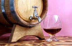 Szkło brandy na tle dębowe baryłki zdjęcia stock