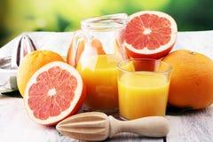 Szkło grapefruitowy sok i plasterki pomarańczowa owoc na drewnianym tle Obrazy Royalty Free