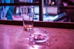 Szkło i ashtray na stole Zdjęcia Stock