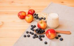 Szkło jogurt, jabłka, borówki i owsów płatki w pucharze na drewnianym stole, obrazy stock