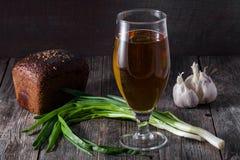 Szkło lekki piwo, bochenek czarny chleb, świeże zielone cebule Zdjęcie Royalty Free