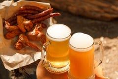 Szkło lekki piwo przeciw tłu zieleni drzewa plenerowi Przekąski kiełbasa, uwędzeni kurczaków skrzydła Fotografia Stock