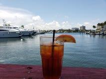 Szkło lukrowy herbaciany napój blisko marina z łodziami obrazy stock