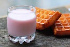Szkło malinowy jogurt i dwa świeżo piec gofra przeciw zamazanemu błękitnemu tłu Obraz Royalty Free