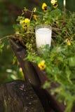 Szkło mleko na drewnianym furgonie otaczającym kwiatami Zdjęcie Royalty Free