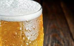 Szkło piwo z kroplami Zakończenie zamazujący tło Obrazy Stock