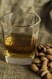 Szkło scotch whisky na wełna worku z migdałowymi ziarnami fotografia stock
