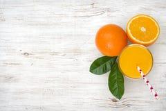Szkło sok pomarańczowy i owoc na rocznika drewnianym tle obraz royalty free