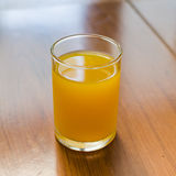 Szkło sok pomarańczowy na stole Obrazy Stock